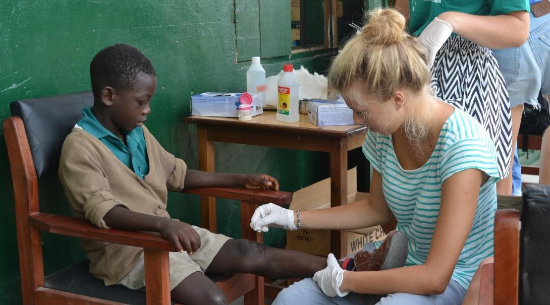 Enfermera interna en Ghana limpiando las heridas de un pequeño paciente.